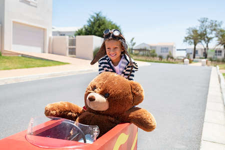 Little kid pushing big toy car and having fun playing with his teddy bear. Teddy bear enjoying pedal race car ride with little boy. Happy child playing with teddy bear and toy car on street. Archivio Fotografico