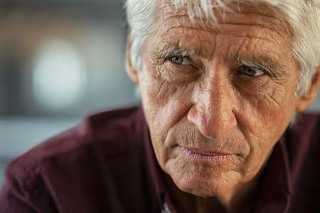 Thoughtful senior man sitting on couch looking away with copy space. Depressed sad man thinking at home. Elderly pensive senior suffering from alzheimer disease. Zdjęcie Seryjne