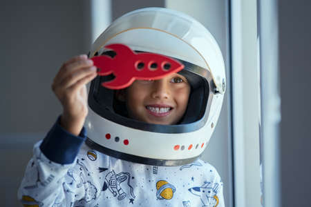 Happy smiling boy wearing an astronaut helmet costume and playing with a spaceship. Child wearing space pajamas and playing with toy rocket near the window. Kid in space dress wearing helmet playing with red toy spaceship at home and dreaming outer space.