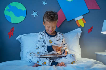 Cheerful boy using digital tablet to search images about solar system and outer space while sitting on bed.
