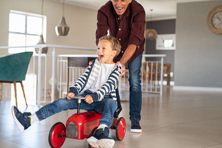 Senior man helping boy ride his toy car at home. Grandfather pushing kid car with little grandson inside to go faster. Excited boy and palyful elderly man playing together at home, copy space. Foto de archivo