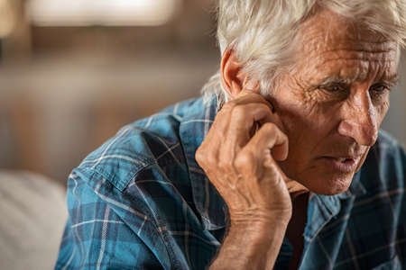 Senior man holding ears while suffering from pain. Tensed mature man sitting at home holding ears.