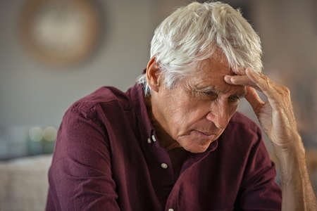 Tired and stressed old man with hand on head sitting at home with headache. Senior retired man at home feeling worried about health problems. Depressed elderly man sitting at home wit head pain suffers from loneliness.