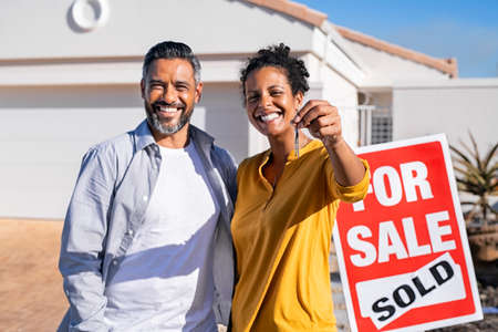 Portrait of happy mixed race couple holding house keys standing near sold signboard. Middle eastern man embracing african woman while showing house key outside of their new home. Proud man and black girfriend moving home after buying their new apartment.