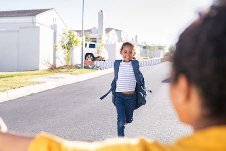 Happy cute little girl running with outstretched arms towards mother outside the house. Young indian schoolgirl feeling happy after first lesson at primary school. Elementary student kid running in the driveway into hands of african mother to hug her after school.