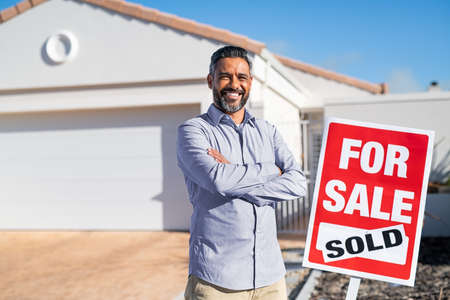 Portrait of confident indian man with crossed arms standing near sold signboard outside new home. Happy satisfied man excited to buy new home looking at camera. Successful mixed race real estate agent purchasing new home for investment purpose with copy space. Stock fotó