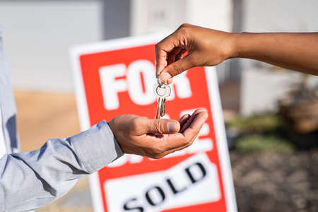 Saleswoman giving home keys to new property owner. Close up of real estate agent hand giving house keys to indian man. Agent giving apartment key to new owner after putting the word sold on for sale sign outside the house.