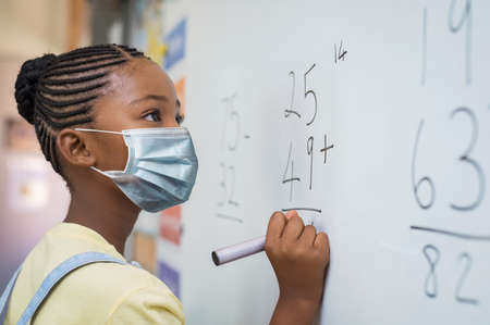 Portrait of african girl wearing face mask and writing solution of sums on white board at school. Black schoolgirl solving addition sum on white board