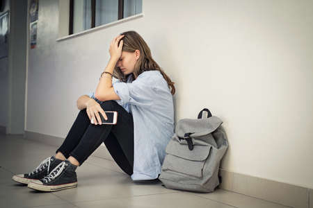 Upset and depressed girl holding smartphone sitting on college campus floor holding head. University sad student suffering from depression sitting on floor at high school. Lonely bullied teen in difficulty with copy space.