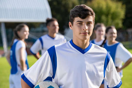 Portrait of young satisfied soccer player holding a football and looking at camera. Young man during training on soccer field with copy space. Proud teen guy training on soccer field with school teammmates in background.