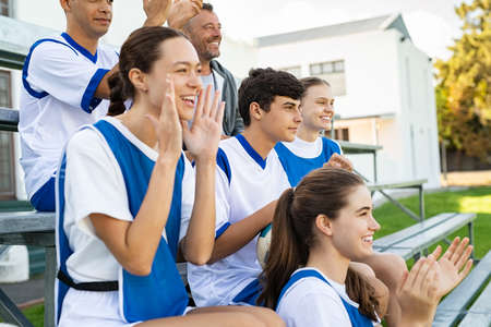 College students cheering for school football team sitting on stands. High school guys and girls clapping hands while watching sport match. Group of fans watching a sports event in the stands of a stadium while encouraging the team. 版權商用圖片