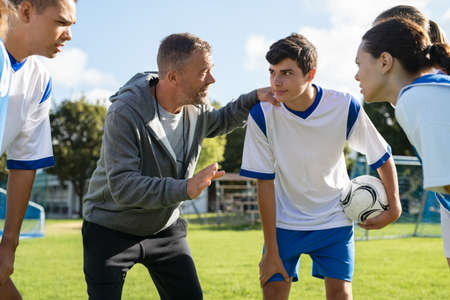 Mature coach teaching strategy to high school team on football field. Young soccer players standing together united and listening coach motivational speech. Coach giving team advise before school match.
