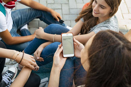 High angle view of young girl reading message on smartphone sitting with group of friends. Close up of young woman typing text message on smart phone with classmates around her. Top view of teen sitting with guys and girls in university campus using mobile phone.