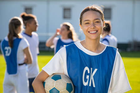 Cheerful soccer player holding a football and looking at camera. Portrait of young woman during training on soccer field. Satisfied high school student holding ball under the arm with her teammmats standing in background.