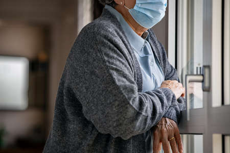 Senior woman wearing face mask standing at window and looking outside during covid-19 pandemic. Old sad woman wearing  surgical mask and looking out of window during coronavirus quarantine. Sad elderly depressed lady stay at home. Banque d'images