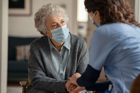 Elderly woman talking with a doctor while holding hands at home and wearing face protective mask. Worried senior woman talking to her general pratictioner visiting her at home during virus epidemic. Doctor explaining about precautionary measures during virus pandemic to old lady and takes care of her. Banque d'images