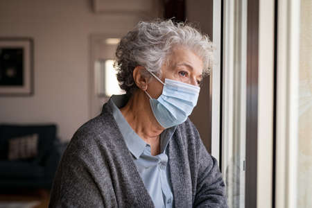Lonely old woman wearing surgical mask standing near window and looking outside. Sad senior lady wearing face protective medical mask and looking through the window. Alone depressed woman stay at home and looking away during quarantine due to the coronavirus. Banque d'images