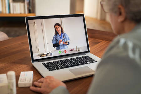 Old woman using laptop in an online consultation with her doctor during home quarantine. Elderly woman sit on table at home while having online consultation on computer with physician during covid-19 outbreak. Old woman patient in conversation with nurse talk on video call using webcam on laptop.