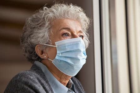 Lonely old woman with grey hair standing near window wearing surgical safety mask during covid-19 virus outbreak. Senior depressed woman wearing  face mask while looking through the window. Close up face of elderly lady in quarantine due to coronavirus. Banque d'images