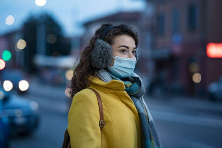 Woman wearing medical protective mask outdoor during dusk. Young woman wearing face mask against pollution standing outdoors on winter evening. Girl with gray earflap in winter city street during coronavirus outbreak.