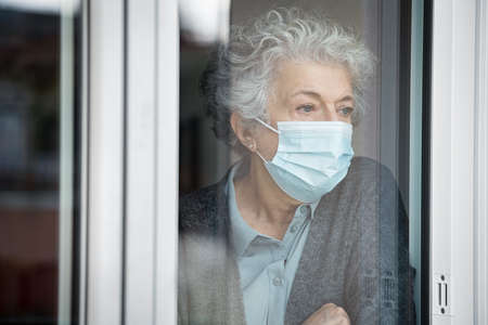 Portrait of lonely old woman wearing surgical mask and looking through the window during lockdown. Senior sad woman with face protective mask stay at home. Depressed and sad lady wearing medical mask sitting near the window at home during the covid-19 pandemic.