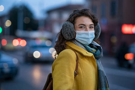 Portrait of happy young woman wearing medical protective mask outdoors and looking at camera. Smiling girl wearing surgical mask for virus protection standing outdoor in winter evening. Smiling girl wearing face mask against smog pollution on urban street at dusk. Banque d'images