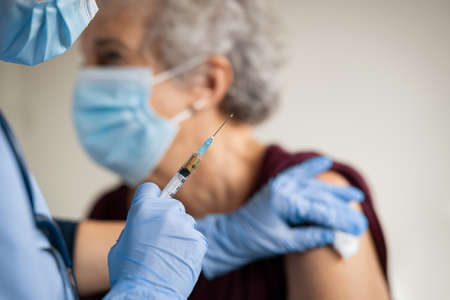 Close up of general practitioner hand holding vaccine injection while wearing face protective mask during covid-19 pandemic. Young woman nurse with surgical mask giving injection to senior woman at hospital. Close up of nurse holding syringe to vaccine old patient from covid19.