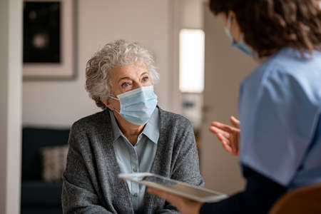 Senior woman wearing safety protective mask at home and talking to nurse holding digital tablet. Back view of young doctor visiting old woman for routine health checkup during covid-19 pandemic. Young general practitioner and elderly patient wearing face masks in a private medical consult during coronavirus and flu outbreak. Banque d'images