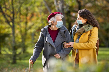 Lovely granddaughter walking with senior woman holding stick in park and wearing mask for safety against covid-19. Happy old grandmother enjoying walking in park with girl. Smiling elderly woman with happy caregiver in park relaxing after quarantine due to coronavirus outbreak and lockdown. Banque d'images