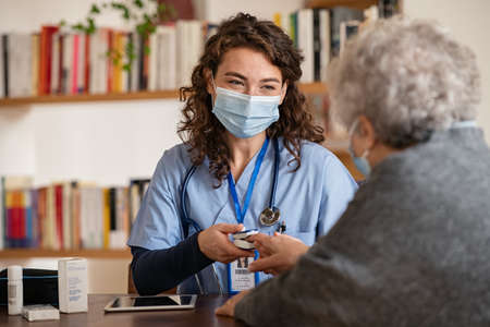 Doctor wearing surgical mask while visiting a patient at home. Senior woman sitting with doctor while doing coronavirus test and screening using oximeter. Rear view of old woman with grey hair giving finger to doctor for oximeter analysis. Banque d'images