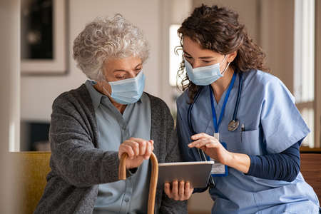 Young doctor and senior woman going through medical record on digital tablet during home visit wearing face protective mask. Old woman holding walking cane sitting with nurse while listen to the covid-19 therapy. Mature woman with doctor wearing surgical mask and using digital tablet during coronavirus pandemic. Banque d'images