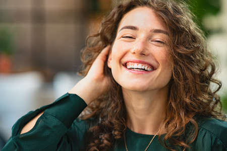 Happy young woman laughing while touching hair. Close up face of smiling girl with curly hair looking at camera. Portrait of carefree businesswoman looking at camera in creative office with copy space.