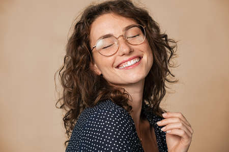 Casual cheerful woman with eyeglasses smiling at camera on cream background. Close up of happy young woman laughing with eyeglasses. Beautiful natural girl having fun with closed eyes showing a big grin. Banque d'images