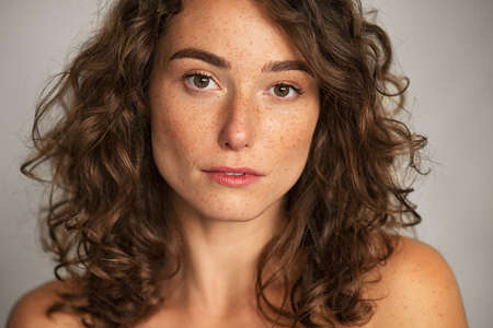 Close up face of beautiful woman with healthy natural skin looking at camera. Portrait of young woman with nude shoulder. Portrait of sensual girl with freckles isolated against gray wall background.