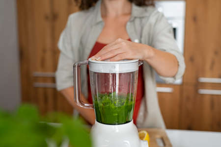 Close up of woman hands making healthy fruit smoothies in her kitchen. Fit girl making healthy detox drink using blender at home. Young woman making green vegan juice using machine. Banque d'images