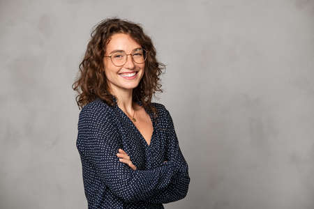 Confident young woman wearing eyeglasses and standing with folded arms on gray wall. Portrait of smiling businesswoman with arms crossed isolated against gray background with copy space. Proud university student girl with specs looking at camera.