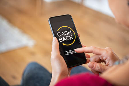 Woman taking benefit of cashback using smart phone, shopping and money refund concept. Woman hand holding smartphone with button to get started the cashback. Close up of girl holding mobile phone while clicking on join now option in app.