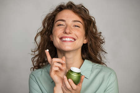 Attractive young woman applying cream on her face full of freckles. Natural girl holding biological and vegan moisturizer jar while looking at camera. Portrait of beauty casual woman with daily lotion for soft hydrated skin isolated on gray background. Banque d'images