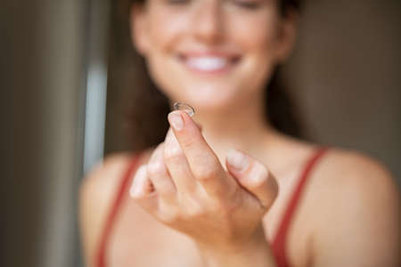 Close up of woman finger holding contact lens in front of her face .. Smiling young woman holding new contact lens on finger tip. Smiling girl holding contact lens, eyesight and eyecare concept.