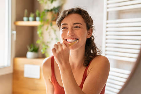 Smiling young woman brushing teeth in bathroom. Portrait of happy girl looking in mirror while using ecological toothbrush with whitening toothpaste. Beauty girl in bathroom cleaning teeth in the morning time.
