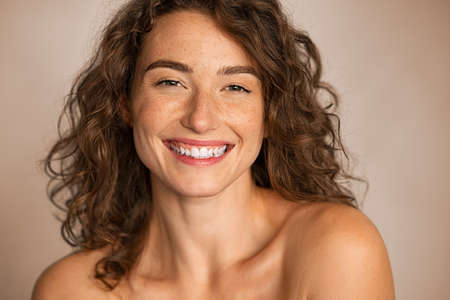 Close up face of smiling young woman with wavy hair looking at camera isolated with copy space. Happy beauty woman feeling good after skin treatment. Portrait of curly hair girl smiling and feeling fresh after spa. Banque d'images