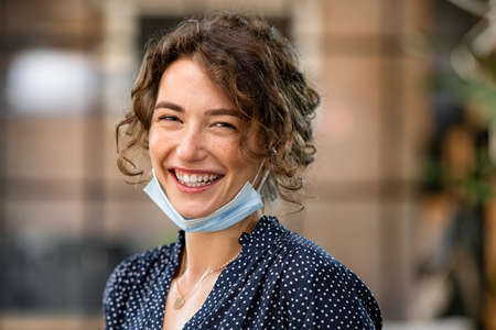Portrait of cheerful young woman with covid-19 protective safety mask. Beautiful businesswoman with toothy smile wearing face mask and looking at camera. Successful girl wearing protective face mask to defeat covid19. Banque d'images