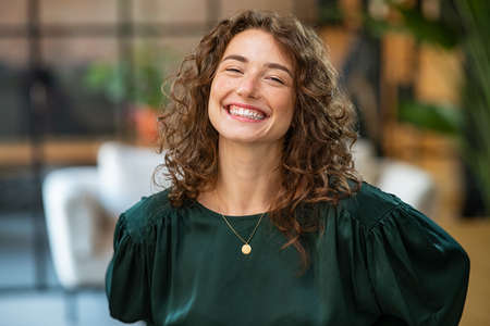 Portrait of beautiful young woman laughing at creative office. Happy businesswoman with curly hair excited with toothy smile. Enthusiastic cheerful girl looking at camera.