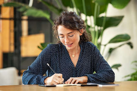 Smiling young woman wearing spectacles and writing on book with pencil. Beautiful girl taking notes on agenda. University student sitting on table and writing an idea. Banque d'images