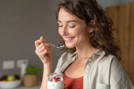 Smiling young woman having a relaxing healthy breakfast at home with fruit and yogurt. Portrait of happy natural girl holding teaspoon with yogurt and blueberries. Beautiful woman eating fresh yoghurt with berries and granola for breakfast at home.