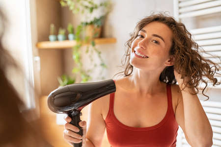 Beautiful girl using a hair dryer and smiling while looking at the mirror. Natural young woman drying curly hair with hair-dry machine. Happy beauty looking at mirror while using hair dryer in the bathroom after shower.