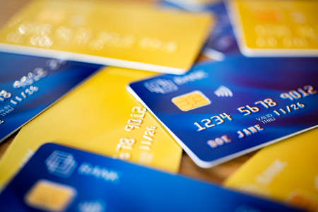 Stack of blue and yellow credit cards and shopping gift cards. Bank cards piled on table. Close up shot of group of debit and credit card: banking, digital payment and consumerism concept.