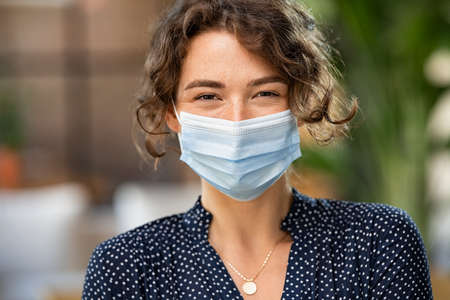 Portrait of happy young woman wearing face medical mask indoor. Hopeful girl with protective face mask looking at camera. Smiling woman wearing safety protective mask to fight against covid-19 pandemic.