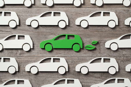 Top view of green electric car with leaves symbol between polluting fossil combustion vehicles. Wooden cut out of single pollution free electric car in the middle of others. Eco friendly, clear ecology driving, no pollution and emmission free transition concept.
