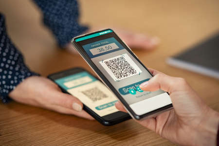 Close up of client hand holding phone and scanning qr code with woman phone to transfer money. Girl hands holding smartphone to scan code for digital payment. Screen scanning with smartphone for qr-code payment.
